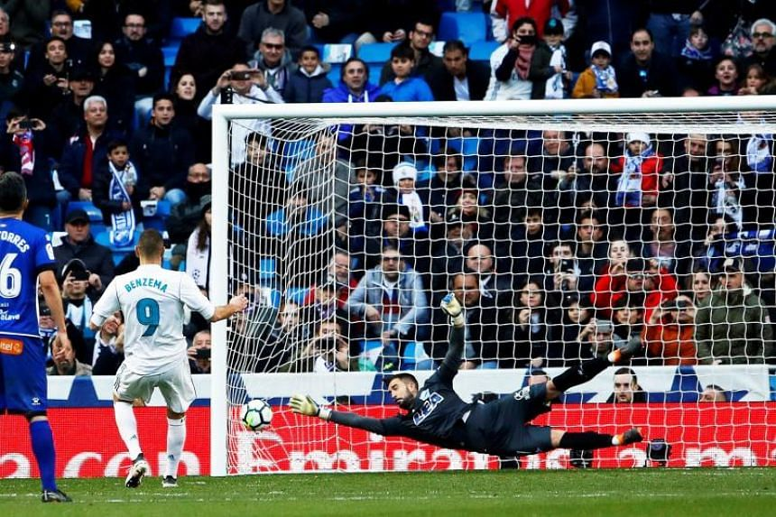 Real Madrid's French striker Karim Benzema (left) scores the 4-0 lead from the penalty spot against Alaves' goalkeeper Fernando Pacheco (right) during the Spanish Primera Division soccer match between Real Madrid and Deportivo Alaves at Santiago Bern