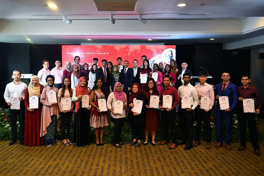 Youths who were appointed ambassadors of peace as part of the Roses of Peace (ROP) Ambassador Programme taking a group photograph with President Halimah Yacob at the Amara Hotel on Feb 25, 2018.