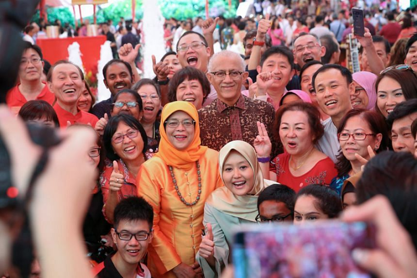 President Halimah Yacob and her Mr Mohamed Abdullah Alhabshee pose for a photo with guests at the Chinese New Year Garden Party at The Istana Lawn.