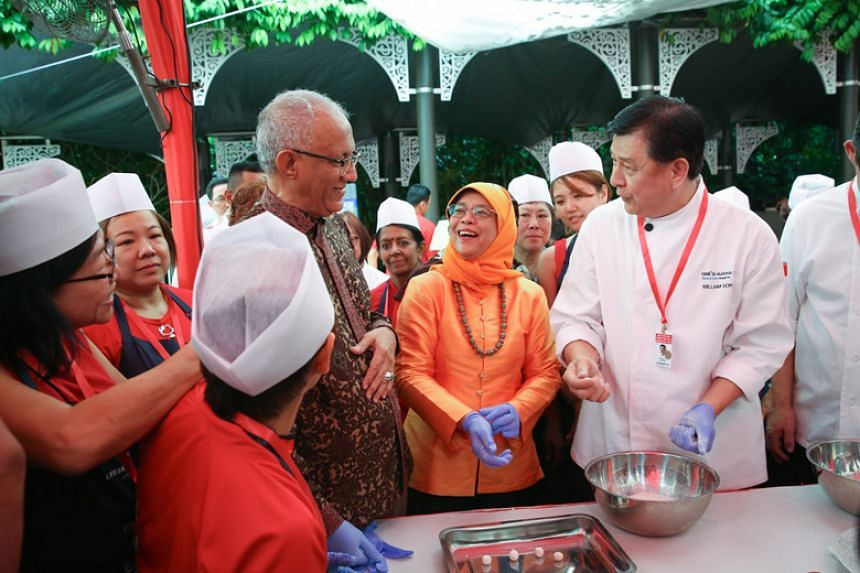 President Halimah Yacob tries her hand at making glutinous rice balls, or tang yuan, at the Chinese New Year Garden Party at The Istana Lawn.