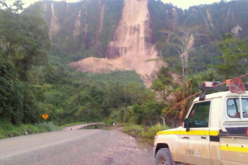 Locals inspecting a landslide and damage to a road located near the township of Tabubil after an earthquake struck Papua New Guinea's Southern Highlands, on Feb 26, 2018.