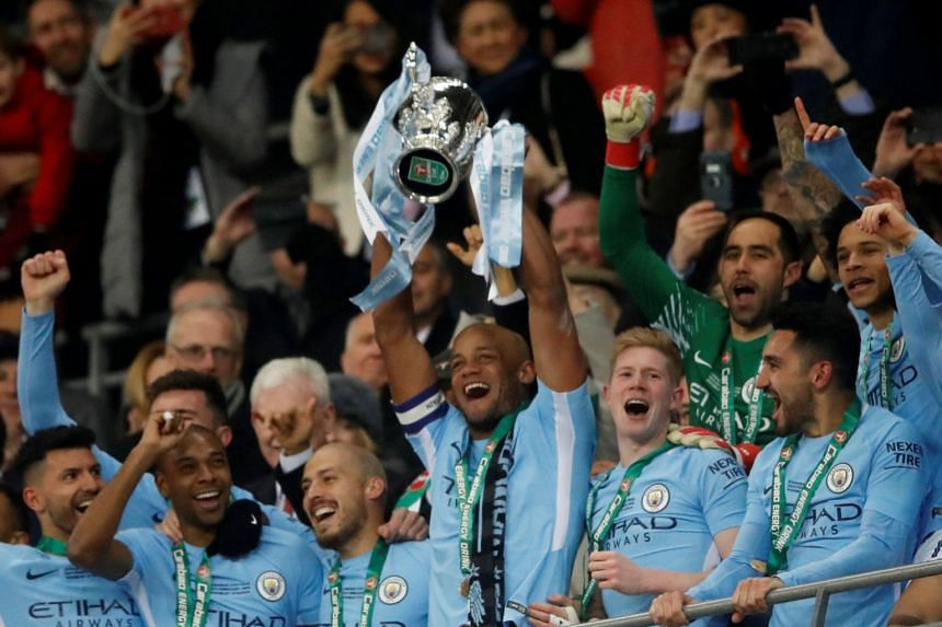 Manchester City's Vincent Kompany lifts the trophy as the team celebrate their win.