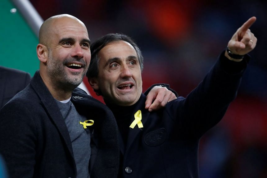 Pep Guardiola (left) celebrates after winning the League Cup.