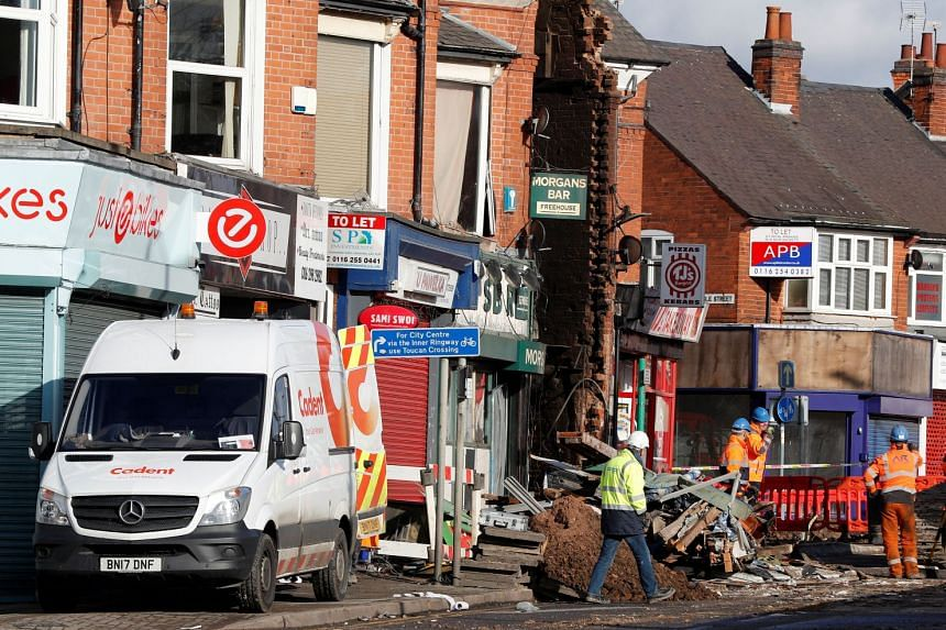 Salvage crews work at the scene of a convenience store and home that were destroyed by an explosion in Leicester.