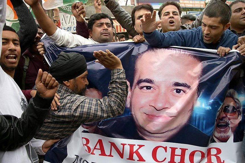 Activists holding a poster of jeweller Nirav Modi during a protest. Mr Modi had successfully built a luxury diamond empire over the past seven years, with outlets the world over, including in the US and China.