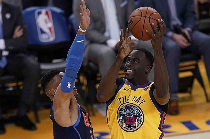 Golden State's Draymond Green going to the basket under pressure from Oklahoma City guard Russell Westbrook. The Warriors forward notched his 2,000th career assist in a 112-80 win for the champions.