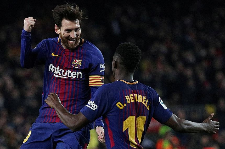Barcelona's Lionel Messi celebrates scoring their third goal with Ousmane Dembele. Off a free kick, he hit the ball under the defensive wall instead of over it.