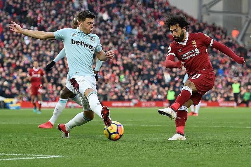 Liverpool's Mohamed Salah shooting between Aaron Cresswell's legs to score Liverpool's second goal against West Ham. He also took the corner from which team-mate Emre Can opened the scoring, bringing the Egyptian's league tally to 23 goals and eight