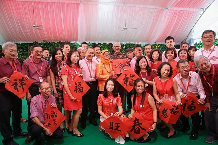 President Halimah Yacob and her husband, Mr Mohamed Abdullah Alhabshee, taking a group photograph with members of the Chinese Calligraphy Society of Singapore at the Chinese New Year Garden Party yesterday. Prime Minister Lee Hsien Loong stopping to