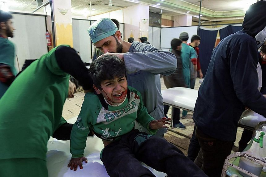 Paramedics tending to the injuries of a Syrian child, who was wounded during reported bombardment by Syrian and Russian warplanes, at a makeshift clinic in the rebel-held town of Douma, in the besieged Eastern Ghouta region of Syria, on Saturday.