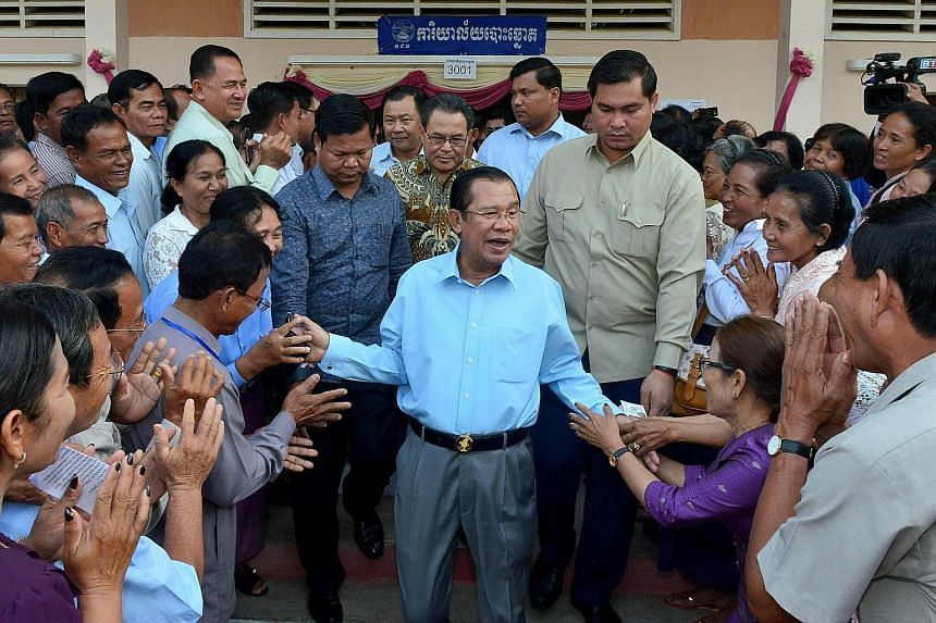 Prime Minister Hun Sen surrounded by commune councillors at a polling station in Cambodia's Kandal province yesterday. The election for the 62-seat Senate arouses little public interest because the Upper House is seen as a rubber-stamp body and candi
