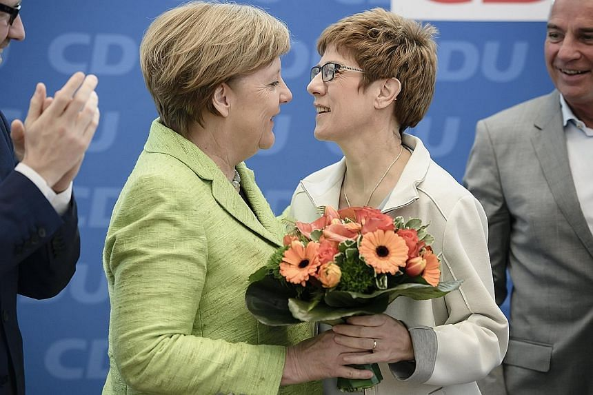 Mrs Annegret Kramp-Karrenbauer and German Chancellor Angela Merkel at a CDU board meeting in Berlin last year. Last Monday, Dr Merkel nominated Mrs Kramp-Karrenbauer as the CDU's secretary-general. The premier of the south-western border state of Saa