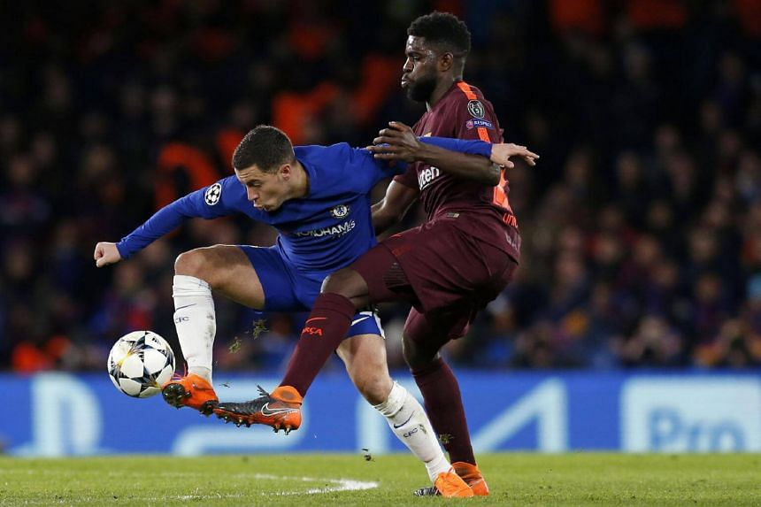Chelsea's Eden Hazard (left) vies with Barcelona's Samuel Umtiti during the first leg of the Uefa Champions League round of 16 football match at Stamford Bridge stadium in London on Feb 20, 2018.