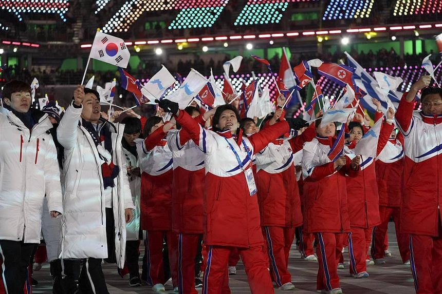 North Korean and South Korean athletes carry their own flags along with the unified Korea flag in the closing ceremony of the 2018 Winter Olympics on Feb 25, 2018.