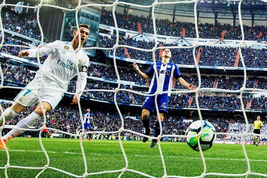 Real Madrid's Portuguese striker Cristiano Ronaldo (left) scores a goal during the Spanish Primera Division soccer match against Deportivo Alaves at the Santiago Bernabeu stadium in Madrid, Spain, on Feb 24, 2018.