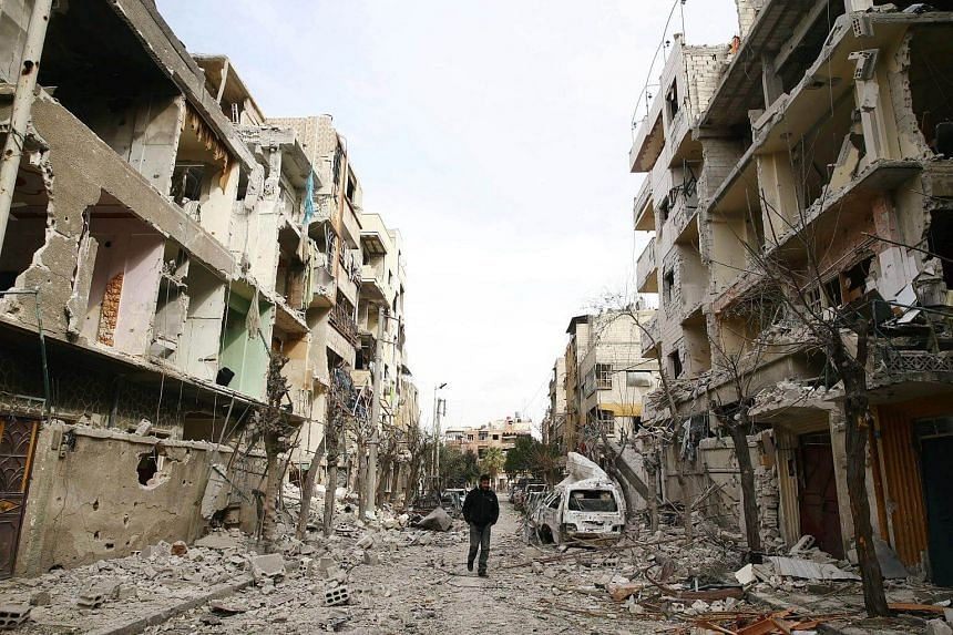 A man walks on a damaged street in the besieged town of Douma, in Damascus, Syria, on Feb 25, 2018.