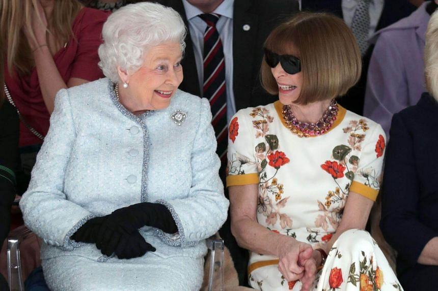 Britain's Queen Elizabeth , dressed in a pale blue suit, sat next to Anna Wintour, editor in chief of American Vogue magazine.