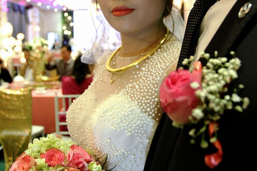 """Vietnamese """"newlyweds"""" Quan and Huong (left) waiting for the arrival of their guests at their """"wedding"""" ceremony in Hanoi on Jan 23, 2018."""