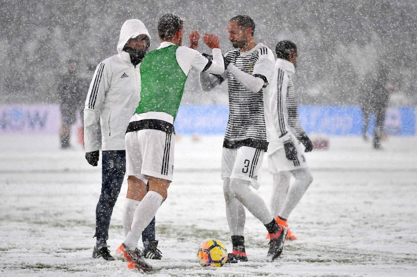 Juventus' players warming up amid heavy snowfall in Turin before their match against Atalanta was postponed.
