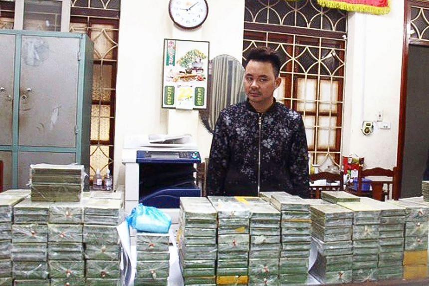 Alleged drug smuggler and ringleader Tran Van Bang stands before heroin bricks seized in the northern province of Cao Bang, on Feb 25, 2018.