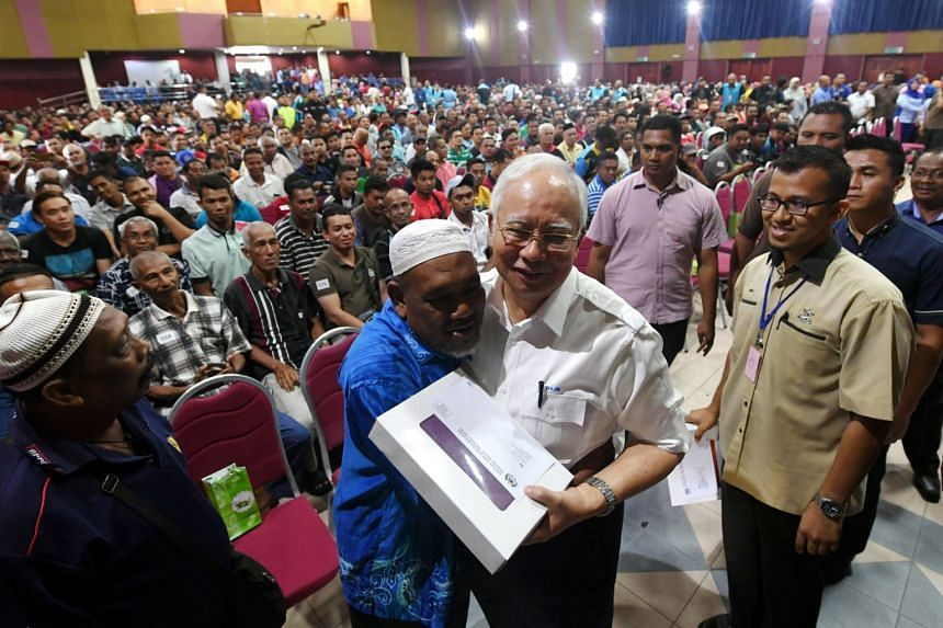 Malaysian Prime Minister Najib Razak being hugged by Harun Abu, 56, one of the recipients of the 1Malaysia People's Aid programme - known by its Malay acronym BR1M - at the launch of this year's scheme in Pekan, Pahang, on Feb 26, 2018.