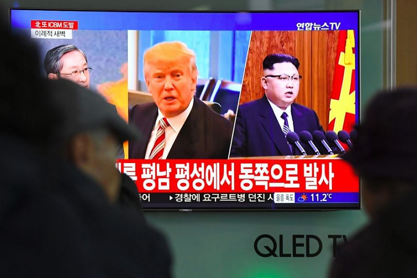 A news broadcast in Seoul shows pictures of US President Donald Trump and North Korean leader Kim Jong Un at a railway station on Nov 29, 2017.