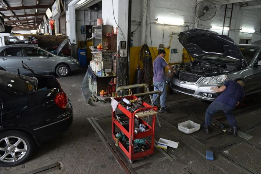 Automotive workers work on a car at a workshop at Sin Ming Drive, on April 24, 2015.