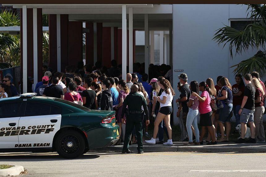 People visit Marjory Stoneman Douglas High School, on Feb 25, 2018 in Parkland, Florida.