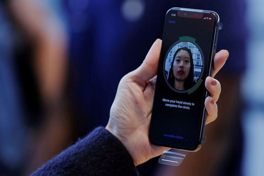 A woman sets up her facial recognition as she looks at her Apple iPhone X at an Apple store in New York.