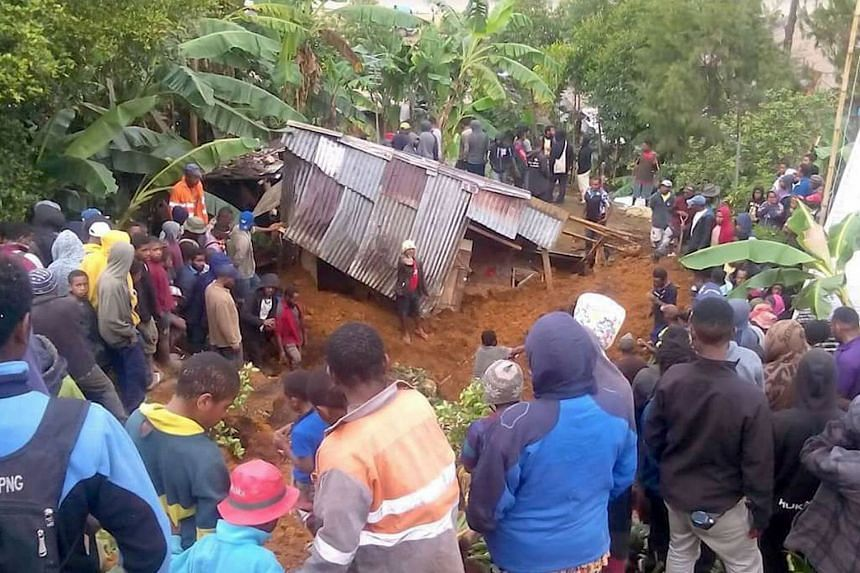 Locals surround a house that was covered by a landslide in the town of Mendi.