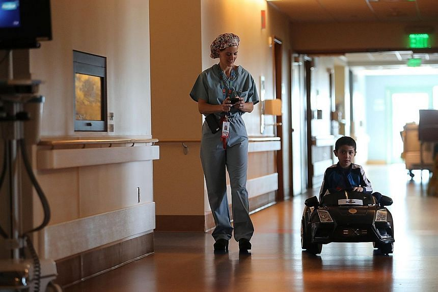 A boy in a remote-controlled car at San Diego's Rady Children's Hospital, which has a programme that uses such cars to take young patients to the operating room. Today, hospitals house MRIs, surgical robots and other technological wonders, yet there