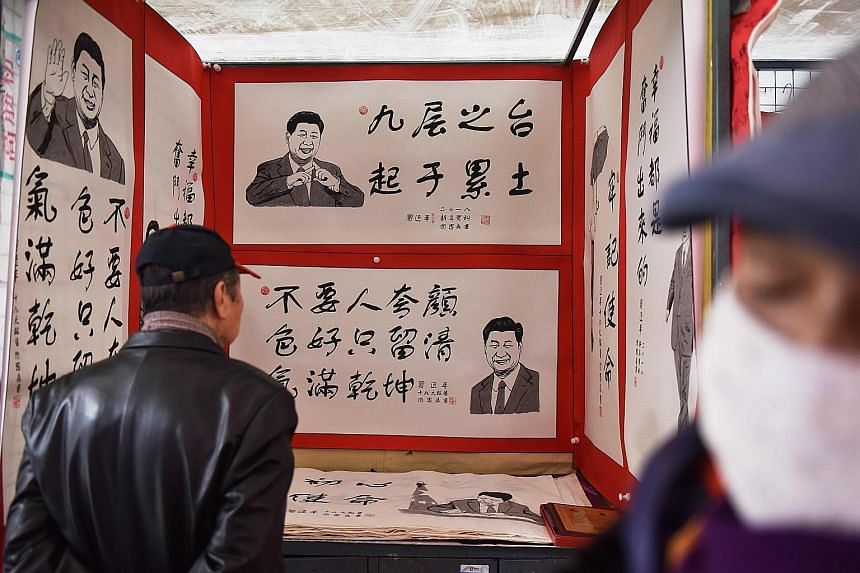 Posters of Chinese President Xi with his sayings at a market in Beijing. To counter online criticism, Web portals of state-linked outlets put out articles saying the masses support the change to the Constitution.