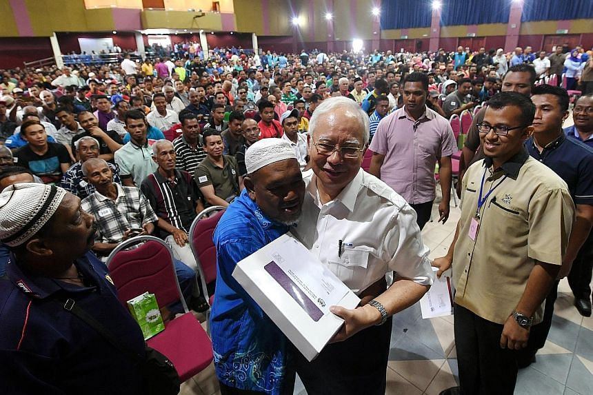 Malaysian Prime Minister Najib Razak getting a hug from Mr Harun Abu, 56, one of the recipients of the BR1M subsidy scheme, at the launch of this year's aid programme in Pekan, Pahang, yesterday.