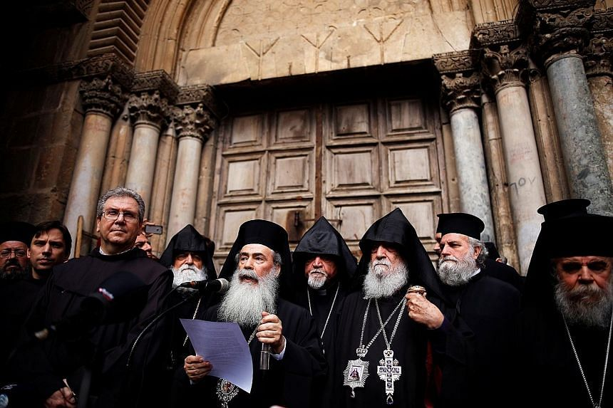 Greek Orthodox Patriarch of Jerusalem Theophilos III speaking at a news conference in front of the closed doors of Jerusalem's Church of the Holy Sepulchre on Sunday.