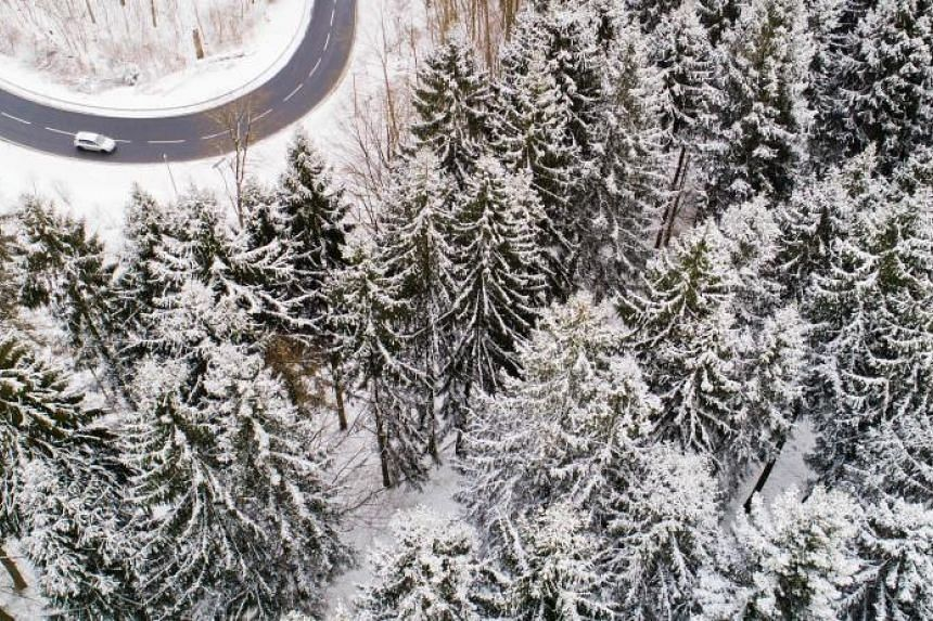 A car driving on a country road through a winter snowy forest in the district of Holzminden, Germany on Feb 26, 2018.