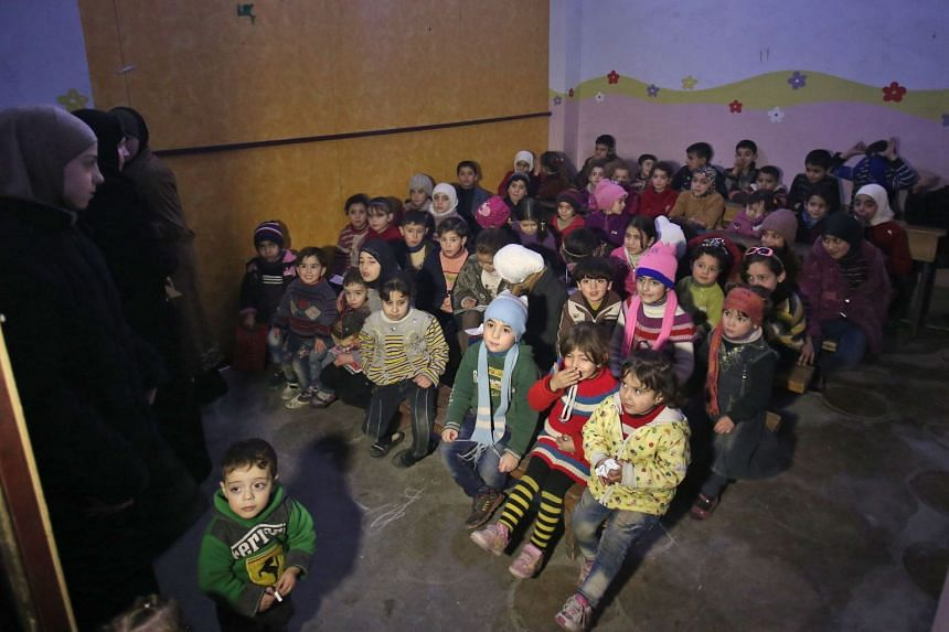 A group of Syrian children who escaped from regime bombardment sitting in a make-shift classroom in Arbin, Ghouta, on Jan 28, 2018.