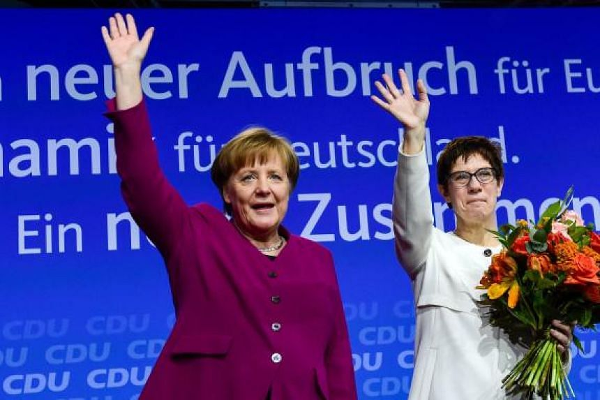 Saarland's State PremierAnnegret Kramp-Karrenbauer (R) and German Chancellor Angela Merkel wave to delegates after Kramp-Karrenbauer was elected new secretary general of the party during the CDU's party congress on February 26, 2018 in Berlin. The C