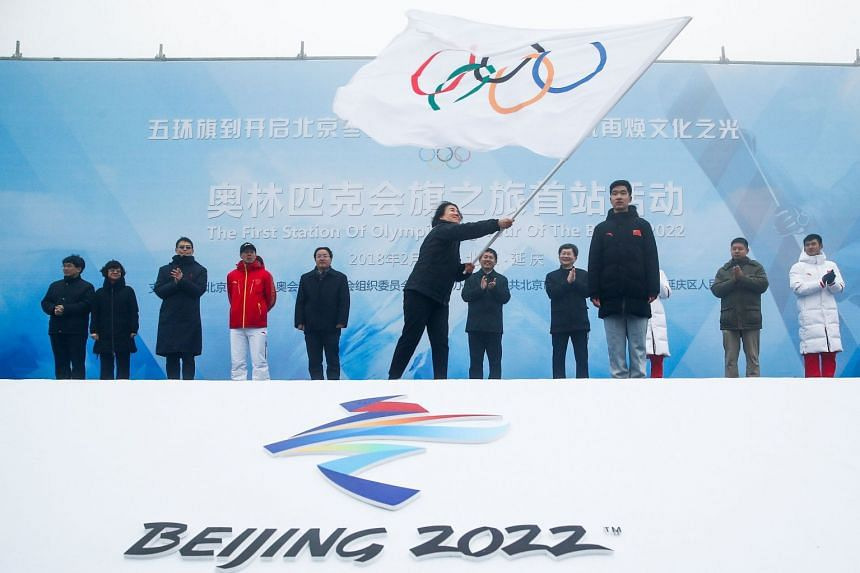 Secretary General of the Beijing Organising Committee for the 2022 Olympic and Paralympic Winter Games, Ms Han Zirong, waves the Olympic flag during a handover ceremony, marking the start of the tour of the flag at the Badaling section of the Great W