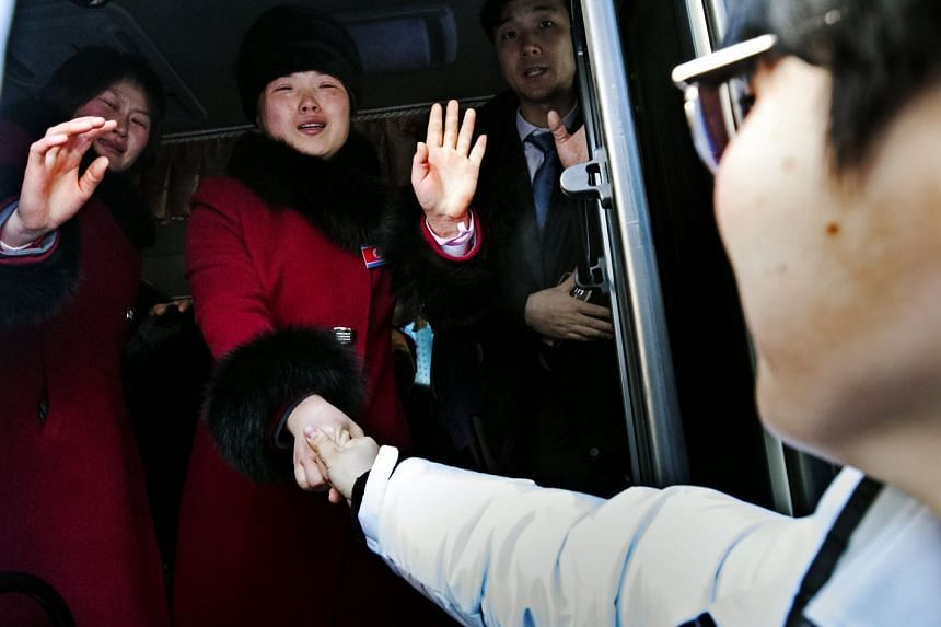 North Korean members of the joint inter-Korean women's ice hockey team bidding a tearful farewell to their South Korean companions yesterday as they left the Gangneung Olympic Village in Gangwon province, after the close of the Pyeongchang Winter O