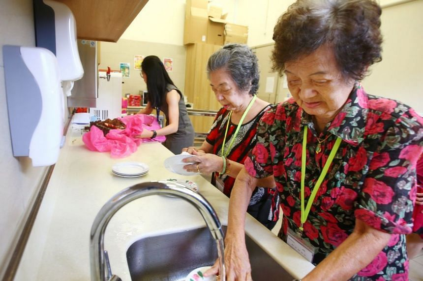 Senior care centre clients Chua Lee Keng (right) and Wee Cheng Eng help wash dishes in the centre.