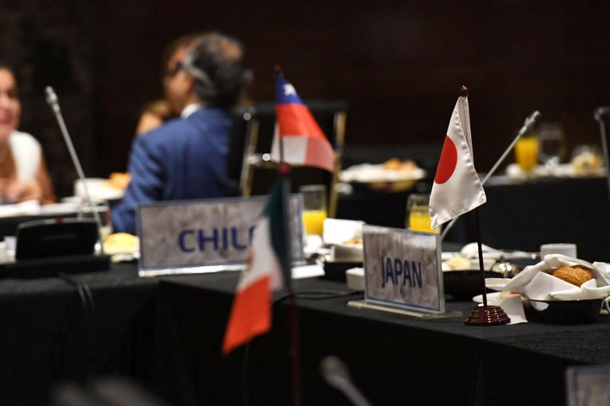 Delegates chat after a TPP11 meeting in Hanoi on May 21, 2017.