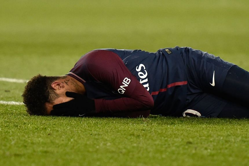 Paris St-Germain's Neymar lies on the pitch after sustaining an injury during the French Ligue 1 soccer match against Olympique de Marseille at the Parc des Princes stadium in Paris on Feb 25, 2018.