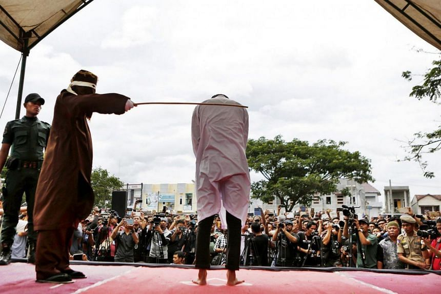 File photo showing a man getting caned in front of a crowd and photographers in Banda Aceh, Indonesia.