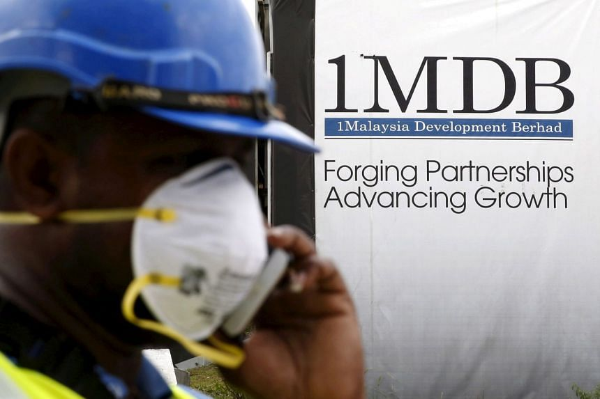 A construction worker talking on the phone in front of a 1MDB billboard in Kuala Lumpur in 2016.