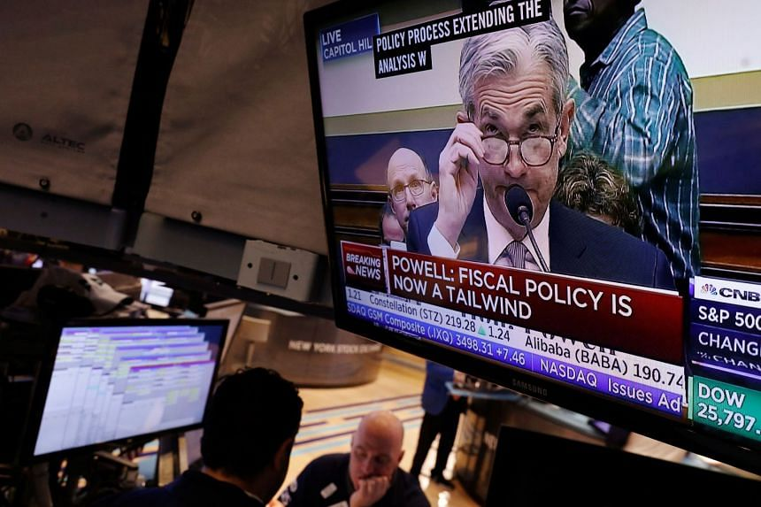 Powell speaking on TV as traders work on the floor of the New York Stock Exchange.