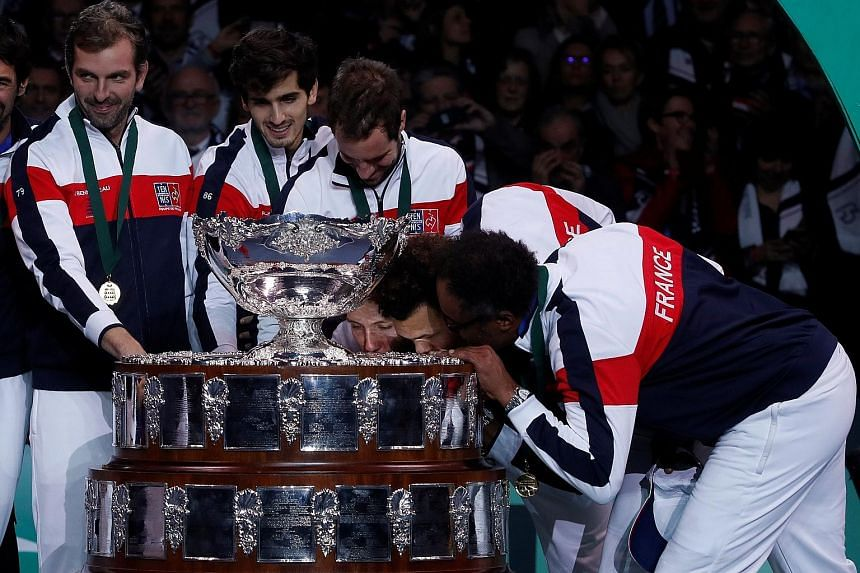 France's captain Yannick Noah (right) and Jo-Wilfried Tsonga kissing the trophy as the rest of the team look on after they beat Belgium in November's Davis Cup final in Lille. The Cup's revamp will see it played in one host city.