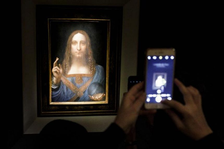 People take pictures of the painting Salvator Mundi, believed to be by Leonardo da Vinci (circa 1500), before an auction at Christie's auction house in New York, USA, on Nov 15, 2017.