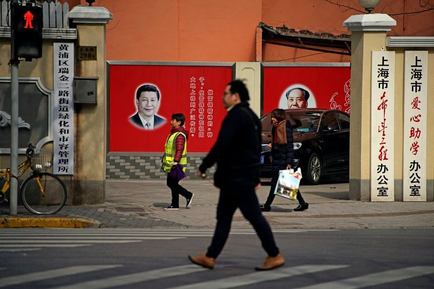 Pictures of Chinese President Xi Jinping and late Chinese Chairman Mao Zedong overlook a street in Shanghai, China, on Feb 26, 2018.