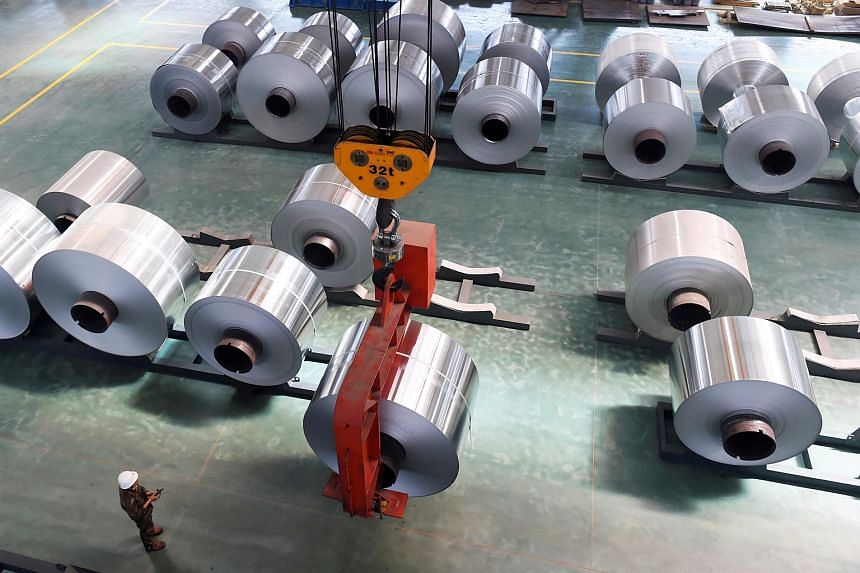 An employee looking at an aluminium foil roll being lifted at a plant in Binzhou, Shandong province, China, on May 16, 2017.