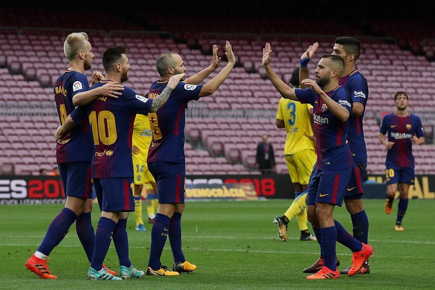 Barcelona's Lionel Messi celebrates scoring a goal with Ivan Rakitic, Andres Iniesta and team-mates in front of the empty stands as the game is being played behind closed doors.